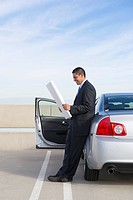 Hispanic businessman looking at blueprints in parking lot