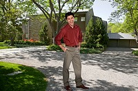 Hispanic man standing in driveway of home