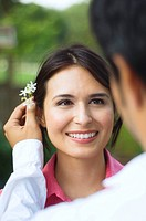Hispanic husband putting flower behind wife´s ear