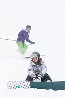 Skier and snowboarder on ski slope