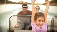 Girl and parents enjoying riding on boat