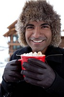 Smiling man drinking hot chocolate outdoors