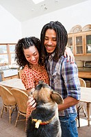 Couple petting dog in kitchen