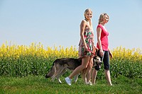two women with dog in landscape