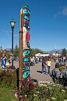 People walk by a totem pole near Raven Hall at Pioneer Plaza at the Alaska State Fair, Palmer, Southcentral Alaska, Autumn