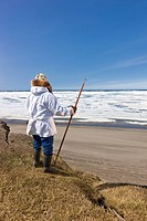 Portrait of a male Inupiaq Eskimo hunter wearing his Eskimo parka Atigi and seal skin hat and holding a walking stick at Old Utkeagvik original town s...
