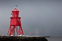 a red lighthouse under a stormy sky along the coast, south shields, tyne and wear, england