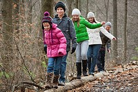 a family walking on a log in a forest during a snowfall, grimsby, ontario, canada