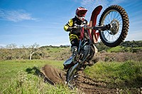Adult male dirtbike rider wheelies motorycle on dirt trail, California