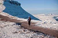 Female hiker hiking path towards Corn Du from Pen Y Fan in winter, Brecon Beacons national park, Wales