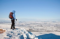 Female hiker in winter looks out from summit of Corn Du, Brecon Beacons national park, Wales