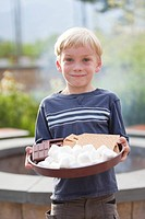 Boy in front of campfire with s´more ingredients