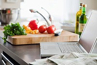 Laptop beside cutting board in kitchen