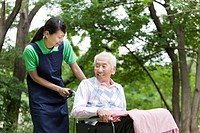 Healthcare worker pushing senior man in wheelchair, Tokyo Prefecture, Honshu, Japan