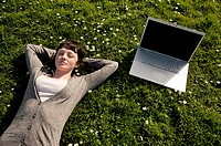 A young woman UK university student with her apple laptop computer outdoors on a sunny warm day