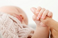 Baby holding mother's hand