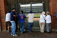 Baseball fans trying to glimpse the Chicago Cubs game in progress thru the locked gate at Wrigley Field in Chicago Illinois