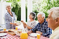 Senior woman serving salad to group of friends