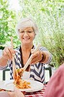 Senior woman putting pasta on friends plate