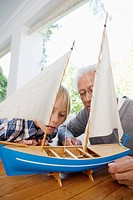 Grandson 10_12 and grandfather examining sailing boat model