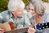Happy senior couple playing guitar on beach