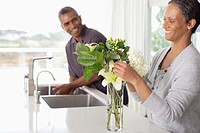 Woman arranging flowers in kitchen, man in background