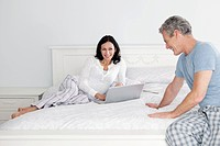 Smiling man sitting on bed, woman using laptop in background