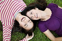 Two women lying on grass
