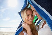 Young couple embracing under towel