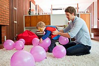 Father and son playing with balloons in living room