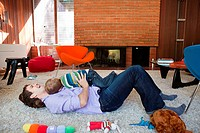 Father playing with son in living room