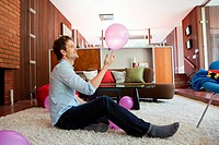 Man sitting on living room floor playing with pink balloon