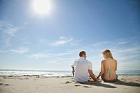 Young couple sitting on sandy beach