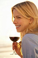 Young attractive woman holding glass of red wine