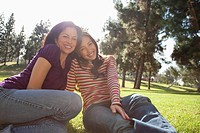 Mother and teenage daughter sitting in park