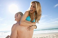 Man and woman messing about on sandy beach (thumbnail)