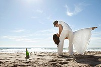 Young couple dancing on sandy beach, with bottle of champagne left in sand