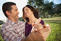 Middle_aged couple dancing in park