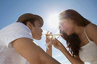 Young couple on beach drinking champagne