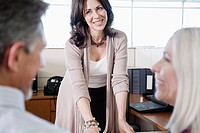 Woman looking at happy couple in office
