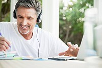 Man listening to music on headphones and writing