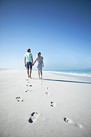 Couple holding hands and walking on beach, footprints on foreground