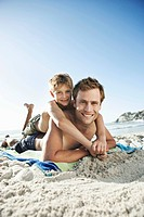 Portrait of happy father and son 10_12 lying on beach