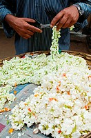 Cutting flower garlands in market in Mysore, Karnataka