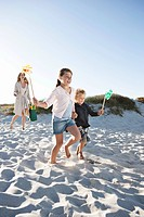 Boy 7_9 and girl 10_12 with mother running on sand dune and holding pinwheel
