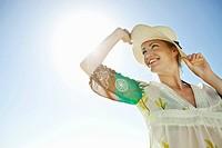Happy woman wearing straw hat against blue sky