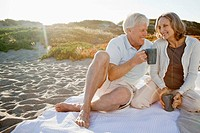 Elderly couple drinking tea at beach
