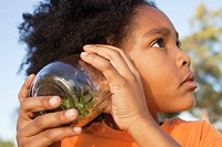 Girl listening to grasshopper in jar