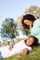 Mother with daughter 13-15 resting on grass in park (thumbnail)