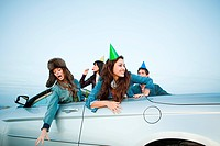 Four young adults wearing party hates in convertible car (thumbnail)